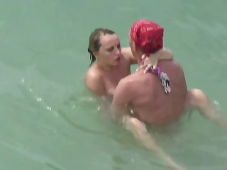 Sex on the beach. Two couples be captivated by in the water.